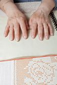 stock photo of braille  - Blind old woman reading text in braille language - JPG