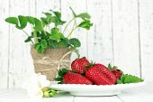 Strawberries with leaves on plate, on wooden background