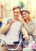 summer holidays, apps and dating concept - couple with bicycles and smartphone in the city