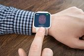 foto of fingerprint  - male hands with white smartwatch with a fingerprint on the screen over a wooden table - JPG