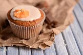 Tasty cupcake with butter cream, on color wooden table, on wooden background