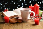 Composition of book with cup of coffee and Christmas decorations on table on dark background
