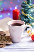 Composition of book with cup of coffee and Christmas decorations on table on bright background