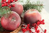 Red apples with fir branches and berries on wicker stand on snow close up