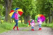 mother and her daughters with umbrellas in spring alley