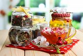 Assortment of herbs, honey and tea in glass jars on wooden table, on bright background