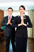Portrait of hotel staff greeting with hands put together