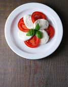 Caprese salad with mozarella cheese, tomatoes and basil on plates, on wooden table background