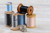 Closeup of antique spools of thread with a needle and thimble on a rustic wooden table. Horizontal f