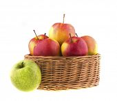 Red and green apples in a wicker baskets, isolated on white.