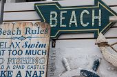image of beach-house  - Painted wooden arrow and signs lead to the beach along with nautical d - JPG