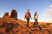 Hikers hiking in beautiful landscape. Hiking couple man and woman trekking walking with backpacks in