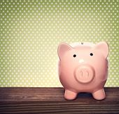 Piggy Bank Over Green Polka Dots Background