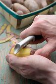 Man peeling potato using peeler