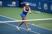 KUALA LUMPUR - APRIL 20, 2014: Timea Babos of Hungary (blue) returns during the doubles final of the