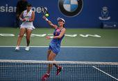 KUALA LUMPUR - APRIL 19, 2014: Zheng Saisai smashes in the semifinals of the BMW Malaysian Open tennis in Kuala Lumpur, Malaysia. Partnering Chan YungJan, they beat Olga Savchuk and Lyudmyla Kichenok.