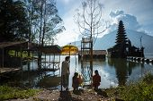 BALI - APRIL 11, 2014: Balinese Hindu devotees go to pray at an ancient temple on Lake Batur, a volc