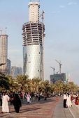 DOHA, QATAR - NOVEMBER 18, 2007: Crowds throng Doha's Corniche after a Red Arrows flying displace, while building work goes on at a frantic rate to create the towers of the city's skyline.
