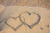 heart on wet golden beach sand