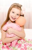 Adorable Smiling Little Girl Playing With A Doll