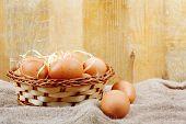 Fresh Chicken Eggs In Straw Nest On Wooden Wall Background