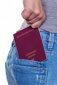 the hand of a young woman pulling a passport out of the pocket of her jeans