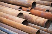 Pile Of Rusted Industrial Steel Pipes Lay On The Ground