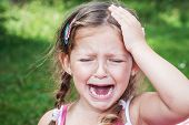 stock photo of cry  - young girl crying with open mouth because of headache