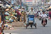 Cyclo driver peddling past garbage