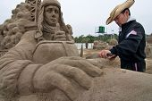 Sand sculpture artist working on his sculpture
