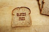 picture of wheat-free  - Bread slice with Gluten Free text on wood surface - JPG