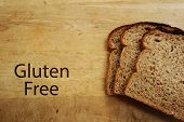 stock photo of wheat-free  - Slices of bread and Gluten Free text on a cutting board - JPG