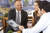 Happy smiling caucasian businessman doing presentation to office workers with tablet computer, outdoor. Suit and tie.