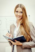 Business woman standing at the office with opened diary and smiling at camera.