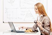 Beautiful businesswoman working in the office with a laptopn and eating cookies.