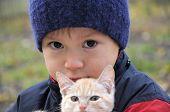 stock photo of catnip  - Boy portrait in warm clothes hugging little kitten - JPG