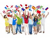 Cheerful Multi-Ethnic Group Of People Standing With Their Arms Raised Holding World Flags.