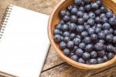 Fresh Wild Berries With Blank Recipe Book On Wood Background