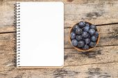Fresh Blueberry Or Blackthorn Berries With Blank Recipe Book On Wood Background