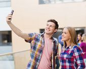 friendship, people, technology and education concept - group of smiling students with smartphone tak