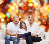 family, childhood, holidays and people - smiling mother, father and little girl reading book over red lights background