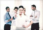 smiling attractive businesswoman in office showing thumbs up