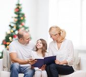 family, childhood, holidays and people - smiling mother, father and little girl reading book over living room and christmas tree background
