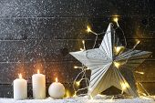 Burning candles,metal star and Christmas lights on wood background.
