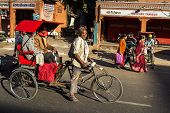 JAIPUR, INDIA - NOVEMBER 25: Rickshaw rider transports passenger early morning on November 25,2012 in Jaipur, India.
