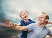 Happy Smiling Son And  Father Portrait Over Blue Sky