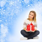 Young girl with gift boxes on blue winter background