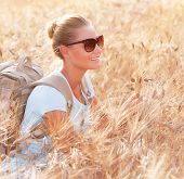 Happy traveler girl sitting with backpack in wheat field, enjoying autumn nature, tracking along Italy, travel and tourism concept