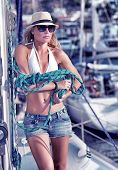 Sexy model posing on sailboat with sailing equipment, happy traveler working on the yacht, luxury su