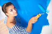Beautiful young woman doing wall painting, standing